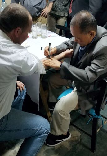 Grand Master Hwang writes on students forearm, creating a tattoo